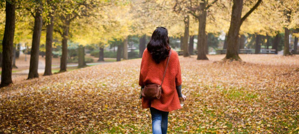 Woman in red coat walking in Autumn leaves